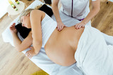Beautiful pregnant woman having a massage in spa.