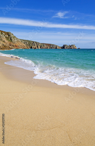 Poster Porthcurno sandy beach and Logan rock in Cornwall England.