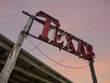 Texas neon sign against evening sky with rustic wood