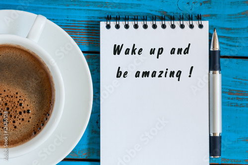 Poster Wake Up and Be Amazing message text written in notepad near morning cup of coffe
