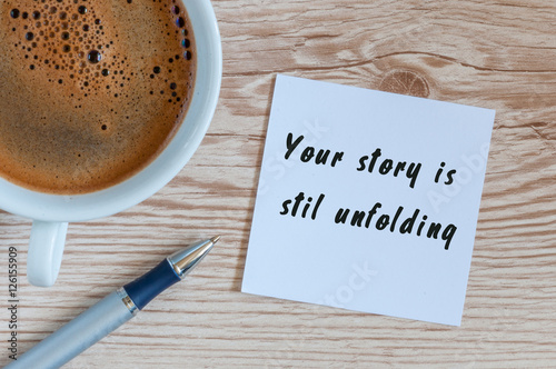 Your Story Is Still Unfolding motivation inscription at notepad near morning cup Poster
