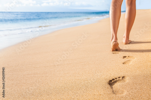 Beach travel - woman relaxing walking on sand beach leaving footprints in the sand. Closeup detail of female feet and legs on golden sand on Kaanapali beach, Maui, Hawaii, USA.