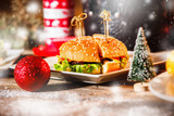 Hamburger on white plate at Christmas style decorated table
