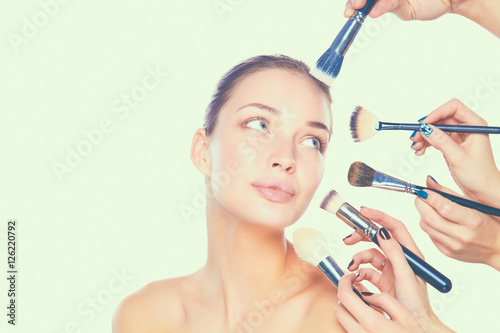 Leinwand Poster Young woman with make up brush, isolated on white background