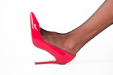 Leg wearing heel shoe. Red footwear with gloss. Femininity and attractiveness. How to emphasize beauty.