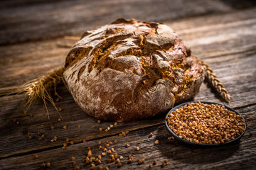 Freshly baked bread on rustic wooden background