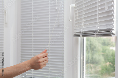Girls hand raise the white blinds with a cord - 126234915