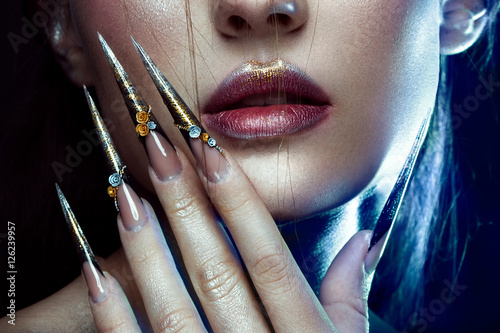 Foto op Canvas Manicure Beautiful girl with creative golden and silver glitter make-up and long nails art. The beauty of the face. Photos shot in studio