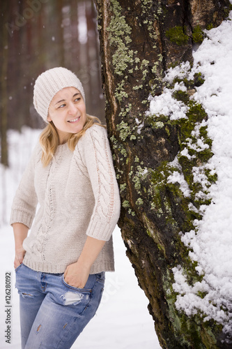 Poster Young blond woman in a warm sweater and a hat standing near a big tree in the forest