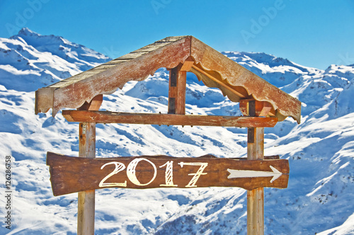 2017 written on a wooden direction sign, snow mountain landscape on the background