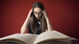 Young attractive brunette tired girl in glasses studying with book