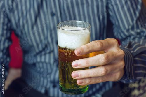 Mano de un hombre joven sujetando un vaso de cerveza Poster