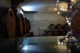 Piwnice winiarni - szklany stół z kieliszkiem przygotowany do degustacji.