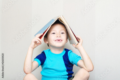 Poster Smiling boy missing milk tooth with book
