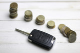 car key and coin on background