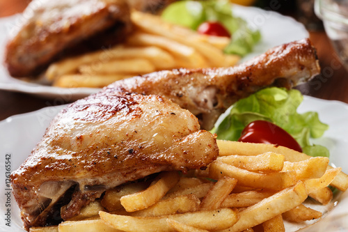 Poster Roasted chicken legs with french fries and lettuce