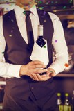 Composite image of midsection of bartender holding wine bottle