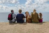 Kvinnor, man och hund njuter av utsikten över havet och horisonten