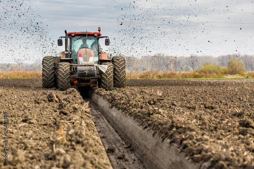 Tractor with double wheeled ditcher digging drainage canal Poster