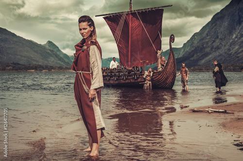 Viking woman standing near Drakkar on seashore Poster