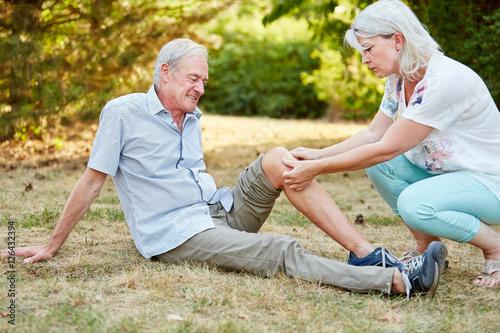 Frau leistet erste Hilfe bei Knieverletzung
