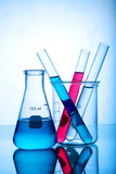 Different laboratory glassware with colored liquid with reflection