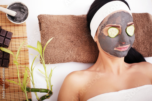 Woman in a beauty salon, wellness. Cosmetic procedure woman's face in the mask mitigating and cucumber slices on eyes © Maksymiv Iurii