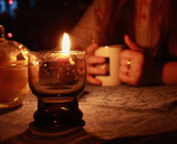 A candle in a glass on a background of a cup of tea in the girls hands