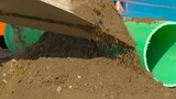 Putting on brown soil on the green pipe in a construction site on a sunny day