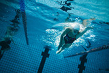 Young female swimmer training in the pool - 126520784