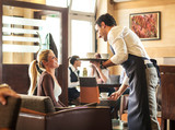 Waiter serves pretty female blond hair guest in cafe.