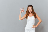 Cheerful young girl showing ok sign with fingers