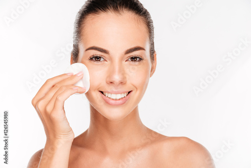 Poster Young beautiful cleaning face with cotton pads