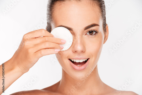 Poster Laughing woman holding round white cotton pad to her eye