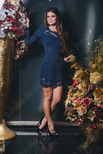 Poster brunette girl posing in blue dress with lace