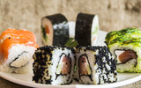 разноцветные суши на белой тарелке