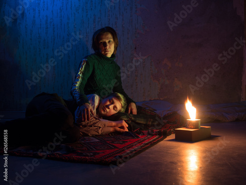 Adult woman sitting on the floor and sadly looks and the young boy sleeping on h Poster