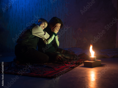 Adult woman sitting on the floor and crying and the young boy put his head on th Poster