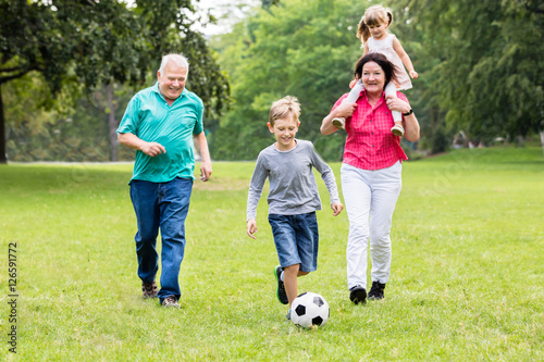 Grandparent And Grandchildren Playing Soccer Ball Together Poster