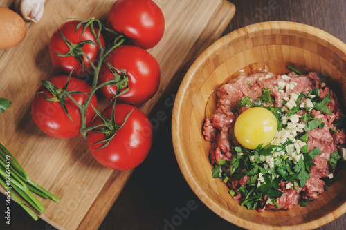 Poster Raw minced meat with egg, herbs and fresh tomatoes on wooden table