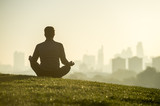 Silhouette of a man sitting in the lotus position meditating on the grassy top of Primrose Hill in front of a misty golden sunrise view of the London city skyline
