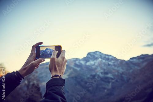 Poster Ragazzo scatta foto in montagna con smartphone