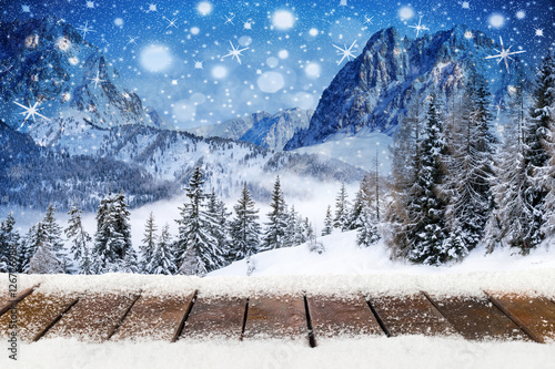 xams christmas background with wooden snowy planks in front of blue nigh sky high mountains with pine trees and shiny stars