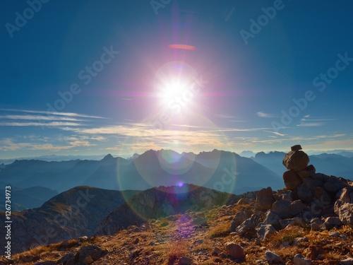 Foto op Canvas Zen Lens flare defect. Balanced stone pyramide on stony peak of mountain.