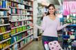 Nice young woman pushing shopping trolley