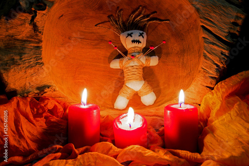 Plakát A voodoo doll with needles stands on an altar with candles