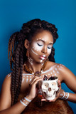 African style woman . Attractive young woman in ethnic jewelry. close up portrait. Portrait of a woman with a painted face. Creative makeup and bright style. fur clothing.skull jewelry