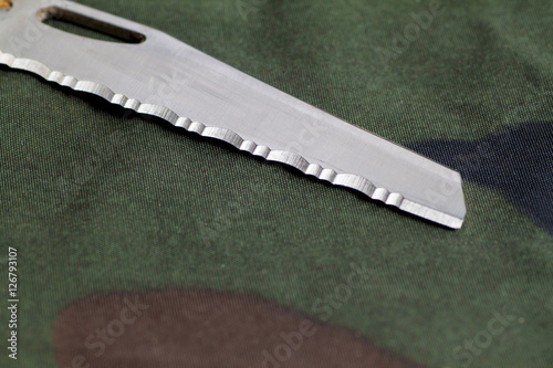 Poster knife on camouflage background