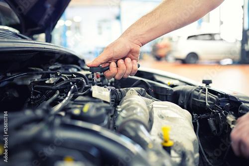 KFZ Mechaniker repariert Motor eines Fahrzeugs in der Autowerkstatt - Close Up Hand mit Werkzeug im Motorraum