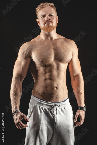 sexy brutal muscular bearded man isolated on black background Poster